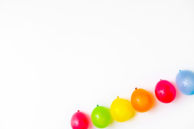 Balões coloridos na parede branca ou vista de tampo da mesa. fundo festivo ou festa. estilo liso leigo. copyspace para texto. cartão de aniversário.