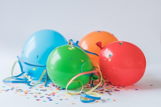 Balões coloridos nos confetes de papel em uma superfície branca