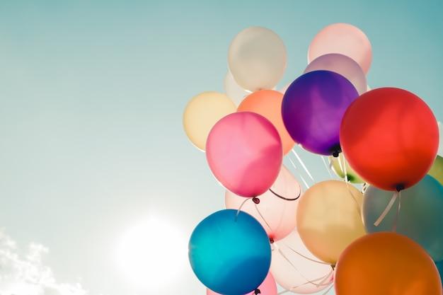 Balões coloridos que voam no céu com um efeito de filtro vintage retro. o conceito de feliz aniversário no verão e festa de lua de mel do casamento - uso para o fundo (tom de cor vintage)