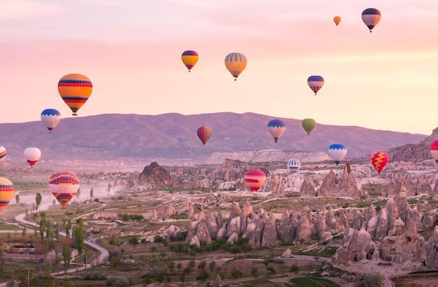 Balões coloridos voando sobre a paisagem rochosa na capadócia turquia