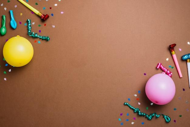 Balões; confete; flâmulas e ventilador de chifre de festa no canto do pano de fundo