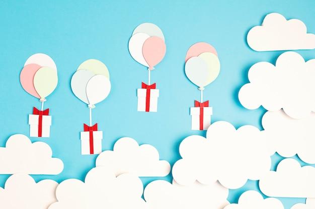 Balões cortados em papel e caixa de presente flutuando no céu azul com nuvens