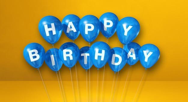 Balões de ar azuis de feliz aniversário em uma cena de superfície amarela