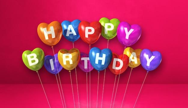 Balões de ar coloridos da forma do coração do feliz aniversário em uma cena de fundo rosa. banner horizontal. ilustração 3d render