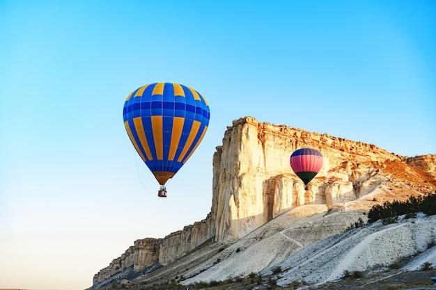Balões de ar coloridos voando em céu claro perto de uma enorme montanha branca em um dia ensolarado