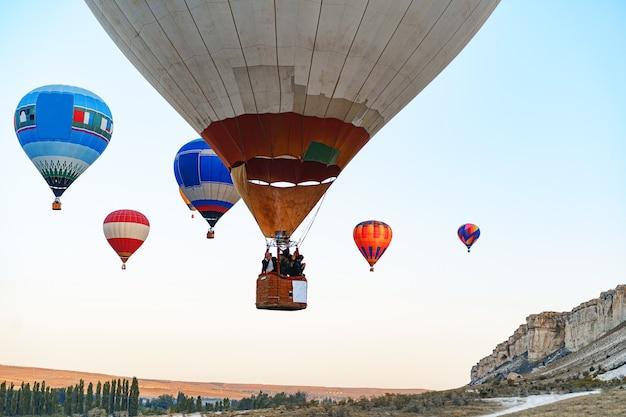 Balões de ar coloridos voando em céu claro perto de uma enorme montanha branca