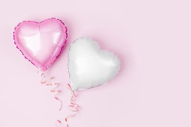 Balões de ar de folha em forma de coração em fundo rosa pastel. conceito de amor. celebração do feriado. decoração de dia dos namorados ou casamento / despedida de solteira. balão metálico