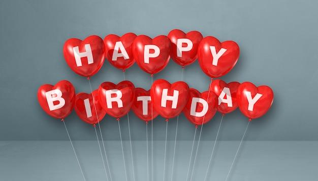 Balões de ar em forma de coração vermelho feliz aniversário em uma cena de superfície cinza