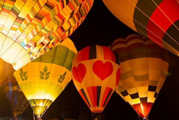 Balões de ar quente brilham à noite flutuar no festival