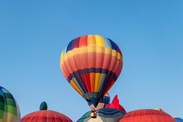 Balões de ar quente coloridos voando com céu azul no festival