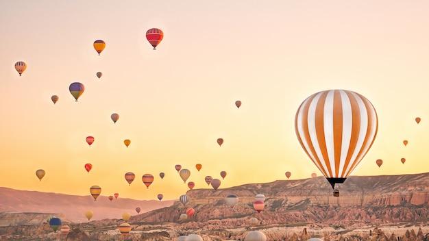 Balões de ar quente coloridos voando sobre a paisagem de rocha na capadócia turquia