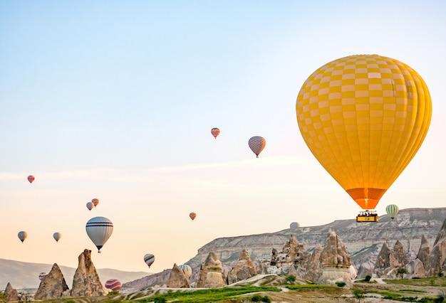 Balões de ar quente coloridos voando sobre a paisagem rochosa na capadócia, turquia