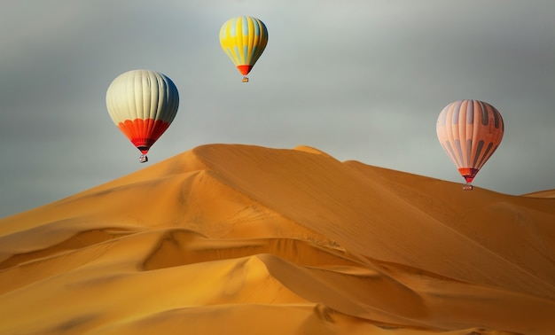 Balões de ar quente coloridos voando sobre as dunas de areia ao pôr do sol