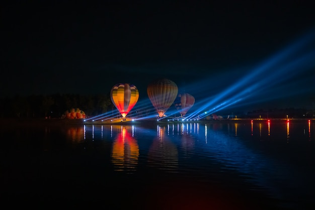 Balões de ar quente coloridos voando sobre o rio no festival da noite