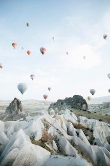 Balões de ar quente que aterram em um parque nacional turquia de cappadocia goreme da montanha.