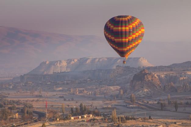 Balões de ar quente que voam sobre a paisagem da rocha em cappadocia turquia.