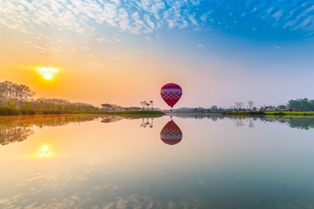 Balões de ar quente voando sobre o campo de flores com o nascer do sol na província de chiang rai, tailândia