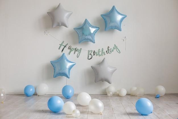 Balões de estrelas azuis e brancas e a inscrição feliz aniversário na parede branca. decoração de aniversário