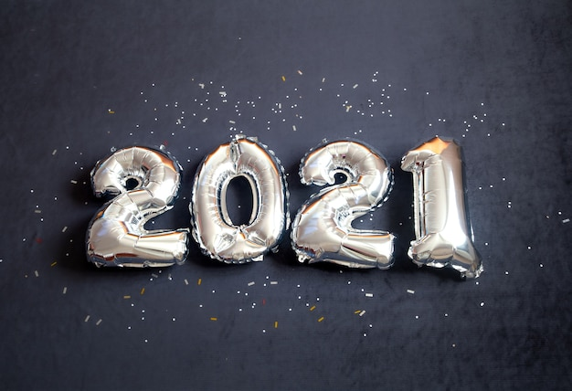 Balões de folha de prata fizeram número de ano novo em fundo preto.