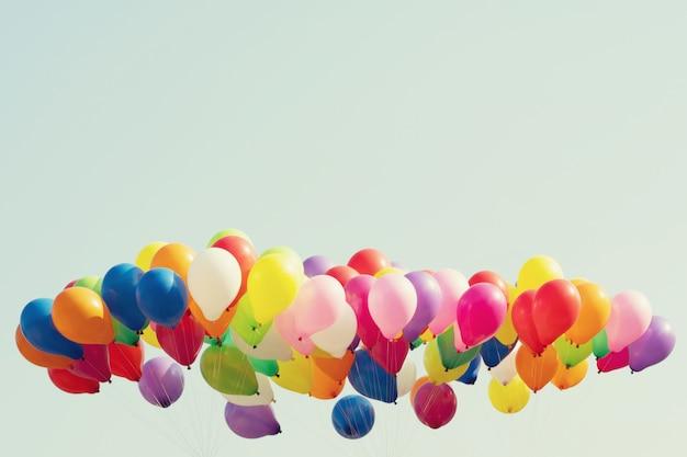 Balões de hélio colorido voando no fundo do céu azul
