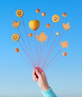 Balões de outono, criativa ainda vida em azul e laranja com biscoitos e folhas de outono nas cordas na mão