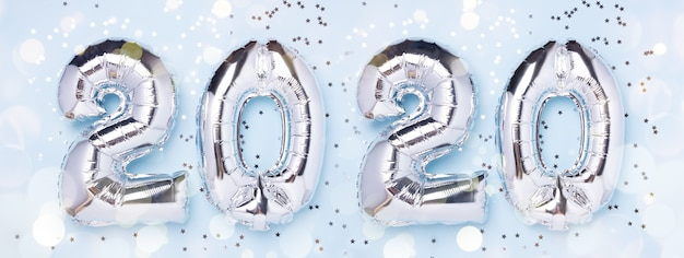 Balões de prata em forma de números 2020 e confetes em azul