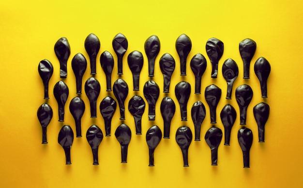 Balões desinflados pretos sobre fundo amarelo.