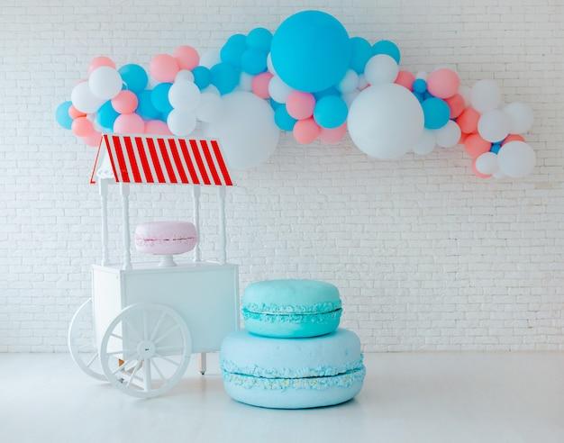 Balões e carrinho de sorvete na parede de tijolo branco
