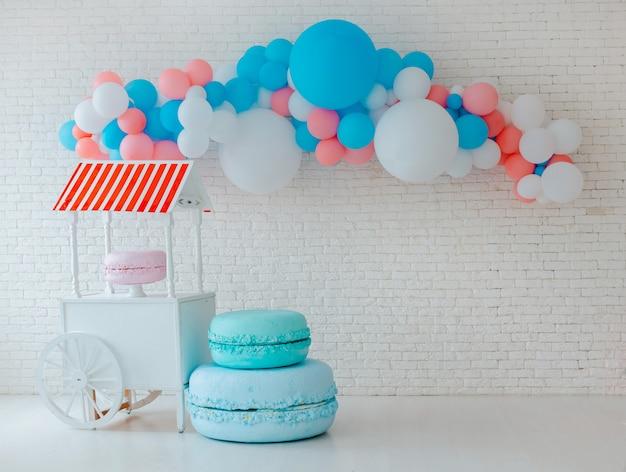 Balões e carrinho de sorvete no tijolo branco festivo