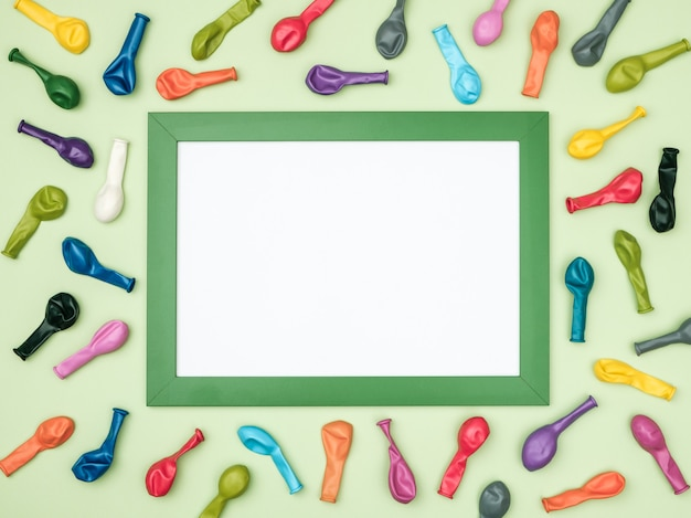 Balões e quadro coloridos na opinião superior do fundo colorido. maquete de aniversário ou festa