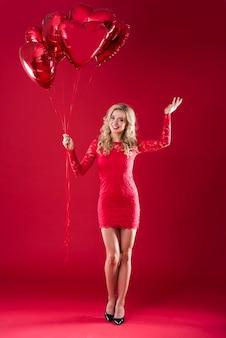 Balões em forma de coração segurados por uma mulher