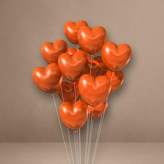 Balões em formato de coração laranja amontoados em uma parede bege