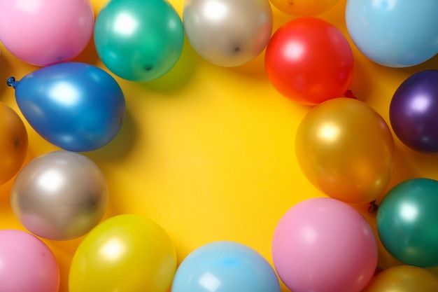Balões multicoloridos em fundo amarelo, espaço para texto