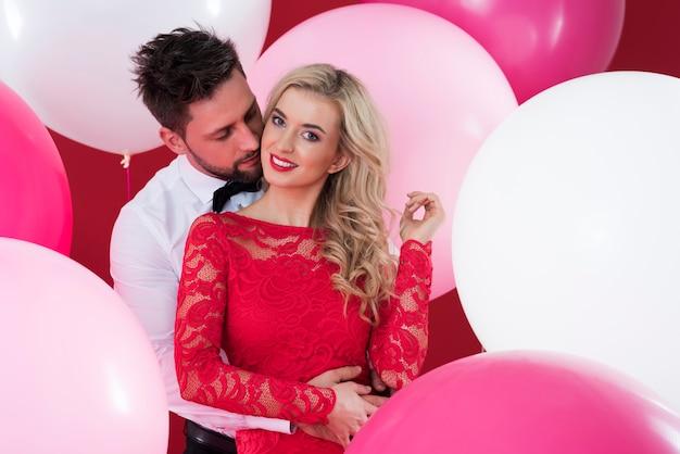 Balões rosa e brancos em volta do casal