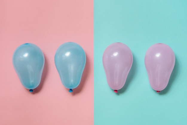 Balões rosa em balões azuis e azuis em fundo rosa. conceito de igualdade de gênero de gênero neutro.