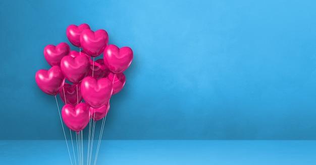 Balões rosa em formato de coração amontoados em uma parede azul