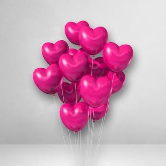 Balões rosa em formato de coração amontoados em uma superfície branca