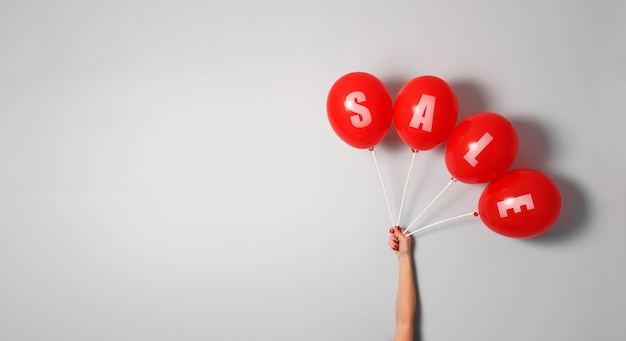 Balões vermelhos com sinal venda na mão da mulher, com espaço de cópia para o seu texto