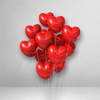 Balões vermelhos em forma de coração amontoados em uma superfície branca