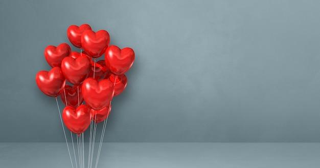 Balões vermelhos em forma de coração amontoados em uma superfície cinza
