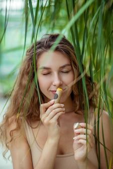 Bálsamo labial. bela jovem segurando um batom de protetor labial e sentindo o cheiro
