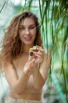 Bálsamo labial orgânico. mulher jovem de cabelos compridos segurando um batom de protetor labial