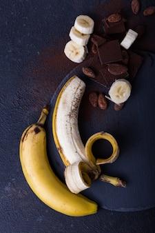 Banan amarelo sobre fundo preto. conceito de comida exótica conceito mínimo de fruta. postura plana.