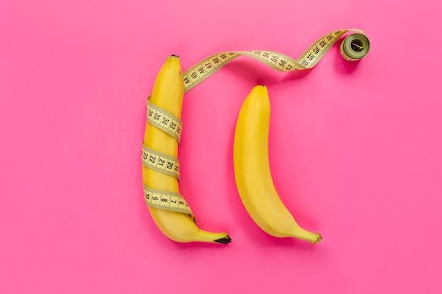 Banana amarela com fita métrica em fundo rosa. conceito de tamanho de pênis de homens. camada plana, vista superior, espaço de cópia.