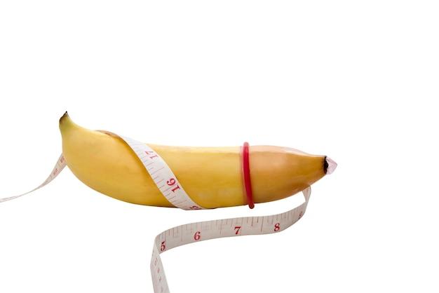 Banana amarela com medição e preservativo, conceito de sexo seguro Foto Premium