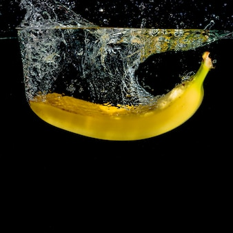 Banana amarela, espirrando água contra o fundo preto