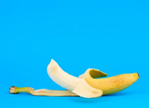 Banana amarela madura descascada em um fundo azul