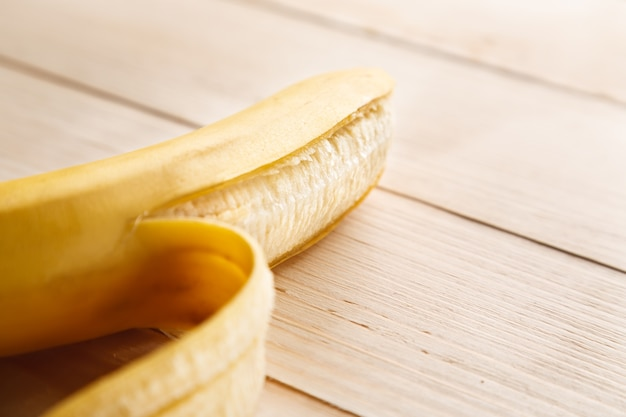 Banana amarela madura parcialmente descascada na mesa de madeira