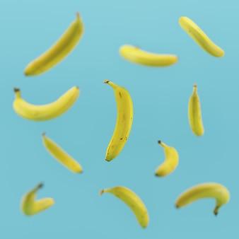 Banana amarela mínima do conceito que flutua no fundo azul