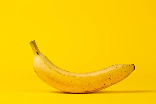 Banana amarela sobre um fundo amarelo. copie o espaço.